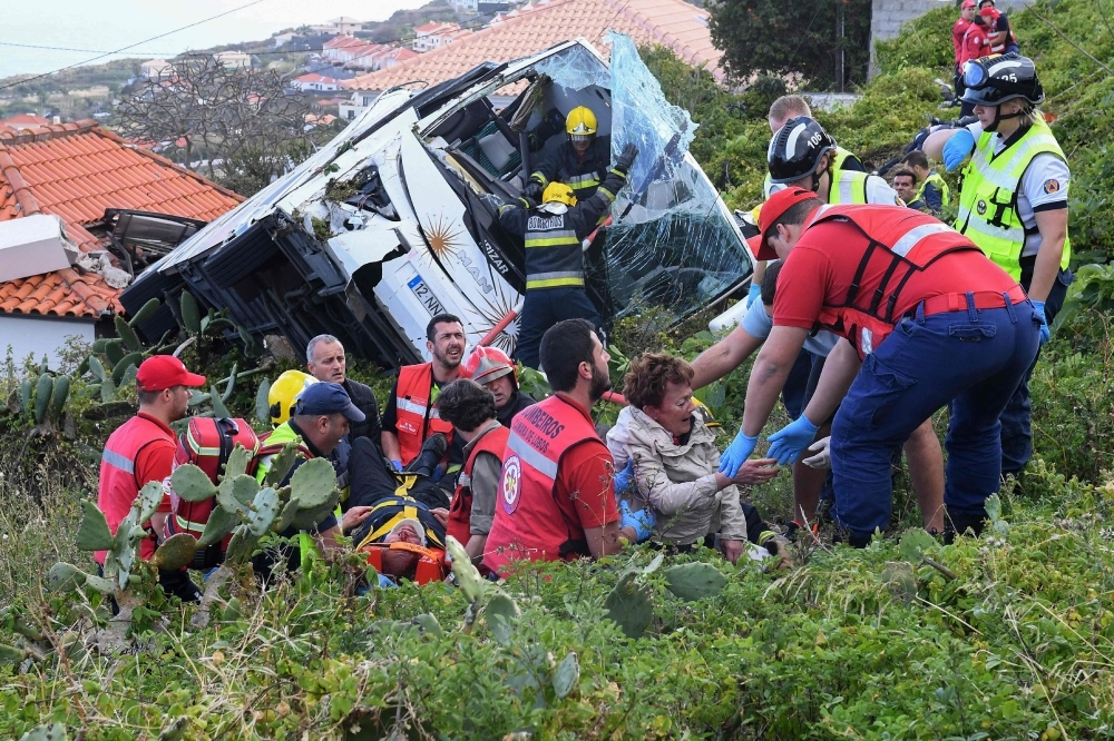 Firemen help victims of a tourist bus that crashed on Wednesday in Caniço, on the Portuguese island of Madeira. — AFP