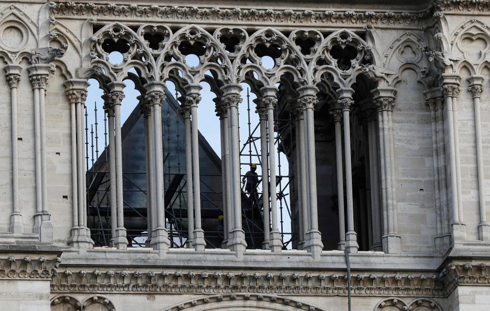 A man works on a scaffold at Notre Dame cathedral on Thursday in Paris. France paid a daylong tribute to the Paris firefighters who saved Notre Dame Cathedral from collapse, while construction workers rushed to secure an area above one of the church's famed rose-shaped windows and other vulnerable sections of the fire-damaged landmark. — AFP