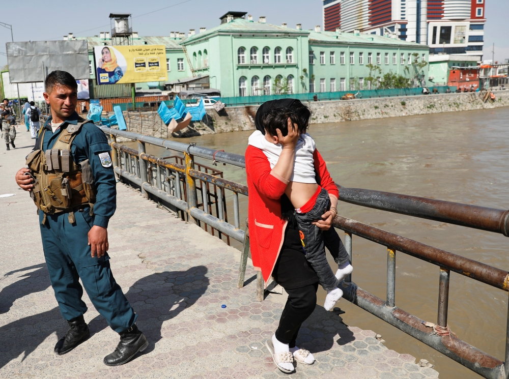 An Afghan woman carries a child rescued from the building of Ministry of Communication and Information Technology in Kabul on Saturday. — Reuters