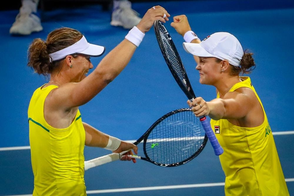 Ashleigh Barty (R) and Samantha Stosur of Australia celebrate their doubles victory of the Fed Cup semifinal against Belarus at the Pat Rafter Arena in Brisbane Sunday. — AFP