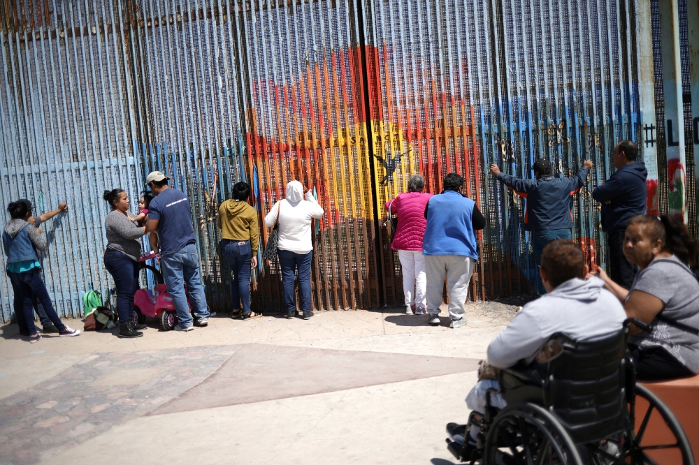 People talk to relatives through the border fence between the US and Mexico in Tijuana, Mexico, Saturday. — Reuters