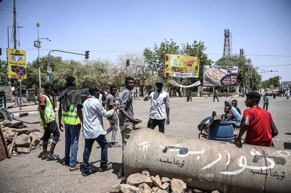 Sudanese volunteers wait in front of a barricade to check protesters during a demonstration outside the army complex in the capital Khartoum, Sunday. Arabic writing on concrete makeshift barricade reads: