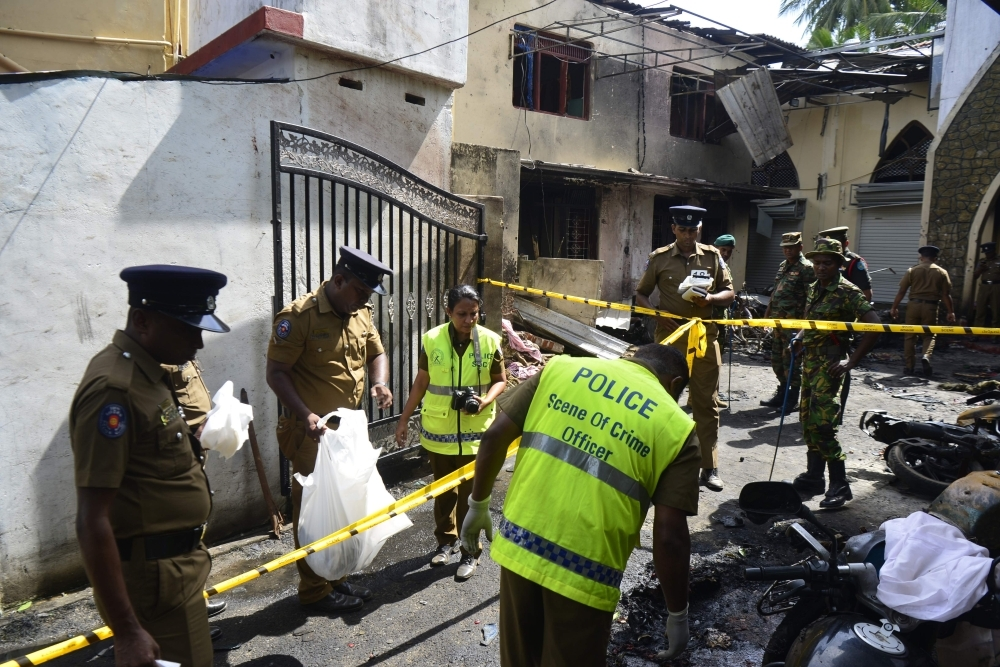 Security personnel and police investigators look through debris outside Zion Church following an explosion in Batticaloa in eastern Sri Lanka, Sunday. A series of devastating bomb blasts ripped through high-end hotels and churches holding Easter services in Sri Lanka, killing nearly 160 people, including dozens of foreigners. — AFP
