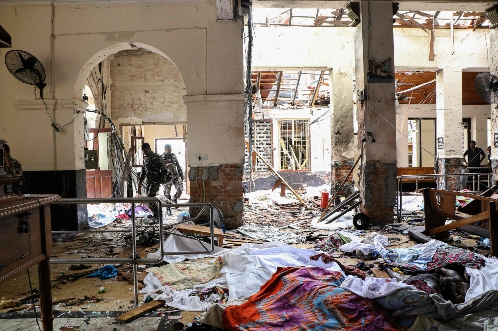 Sri Lankan security personnel walk next to dead bodies on the floor amid blast debris at St. Anthony's Shrine following an explosion in the church in Kochchikade in Colombo on Sunday. — AFP