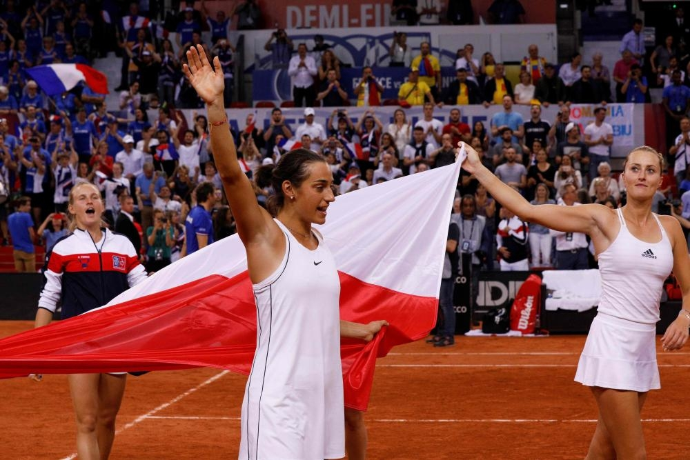 Kristina Mladenovic (R) and Caroline Garcia of France celebrate after winning the fifth rubber of the Fed Cup tennis semifinal match against Romania at The Kindarena in Rouen Sunday. — AFP
