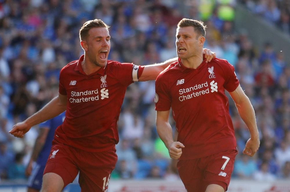 James Milner of Liverpool celebrates scoring their second goal with Jordan Henderson during their Premier League match against Cardiff City in Cardiff Sunday. — Reuters