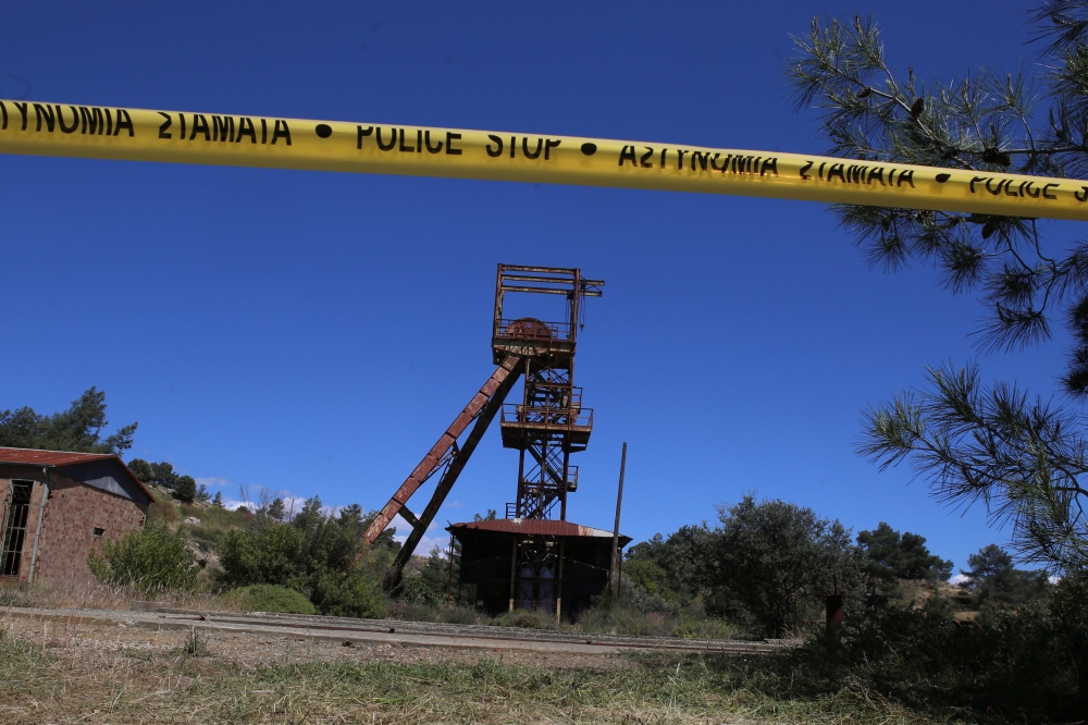 A police line tape secures the area around a mine where two women were found dead, near the village of Mitsero in Cyprus, on Monday. — Reuters
