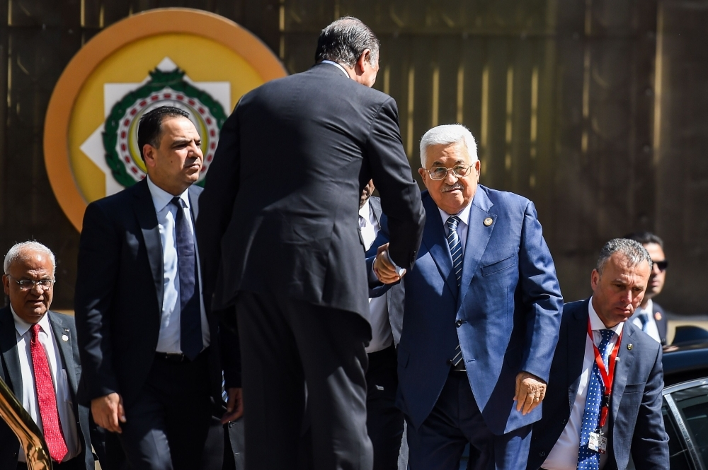 Palestinian president Mahmoud Abbas (C) is greeted upon his arrival at the Arab League headquarters in the Egyptian capital Cairo, to discuss the latest developments in the Palestinian territories on April 21, 2019.  / AFP / MOHAMED EL-SHAHED