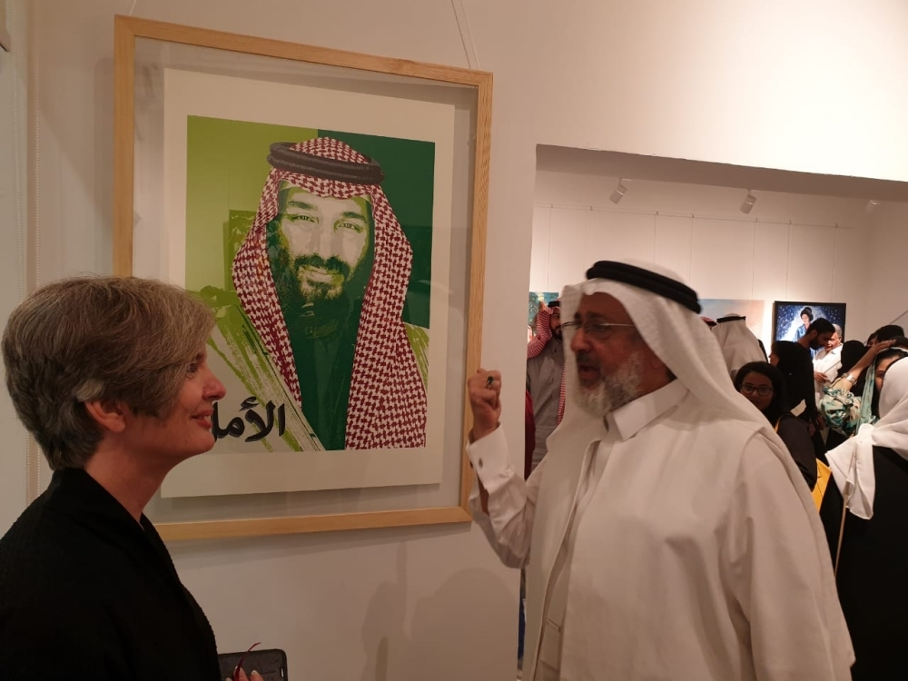 "Saudi artist Hisham Binjabi speaking to Al-Jawhara about the Hope poster during the ""Nawat Al Fun Members"" exhibition."