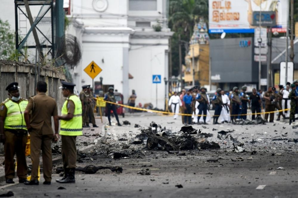Sri Lankan security personnel inspect the debris of a car after it explodes when police tried to defuse a bomb near St. Anthony's Shrine in Colombo on Sunday. — AFP
