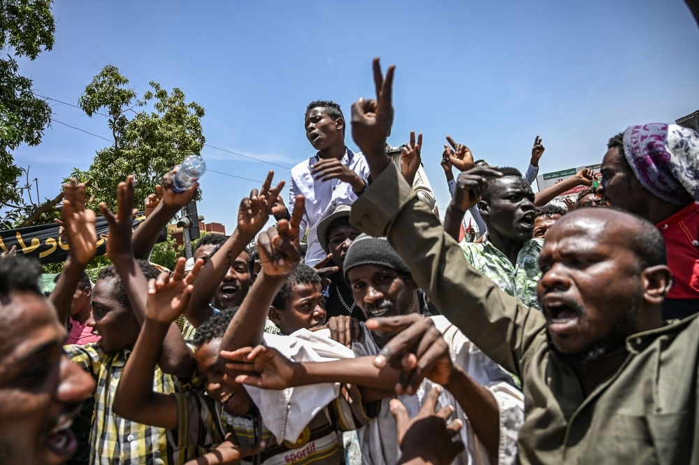 Sudanese protesters shout slogans and flash the victory gesture during a protest outside the army headquarters in the capital Khartoum on Monday. — AFP