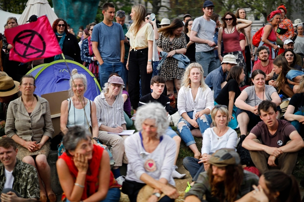 Climate change activists gather together at the Extinction Rebellion group's environmental protest camp at Marble Arch in London on Monday, on the eighth day of the group's protest calling for political change to combat climate change. — AFP