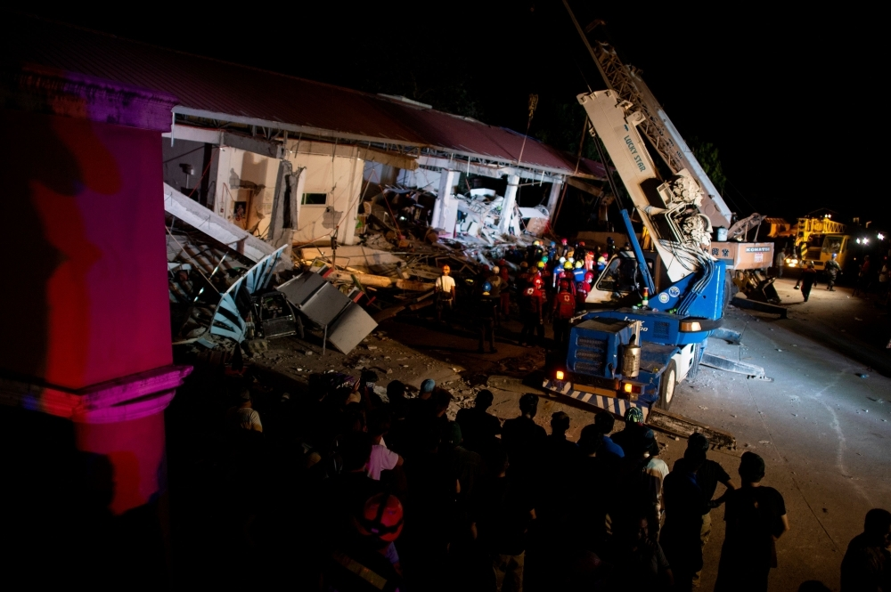 Rescue workers search for survivors in a collapsed Chuzon Super Market in Porac, Pampanga, after a powerful earthquake hit northern Philippines, on Monday. — AFP