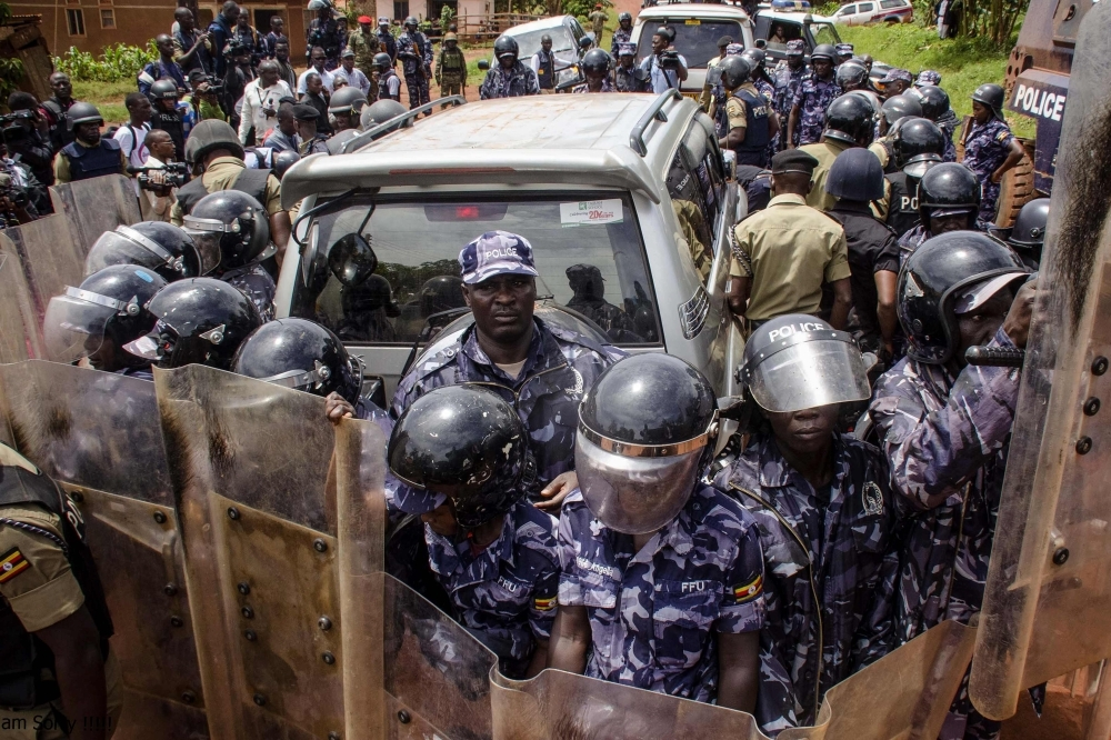 Police officers surround the car of Ugandan musician turned politician Robert Kyagulanyi, commonly known as Bobi Wine, before his arrest on his way to a press conference held to announce the cancellation of his show at Busabala, Uganda, on Monday. — AFP