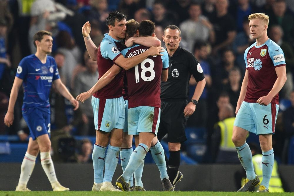Burnley's players celebrate the point against Chelsea during their English Premier League match at Stamford Bridge in London Monday. — AFP
