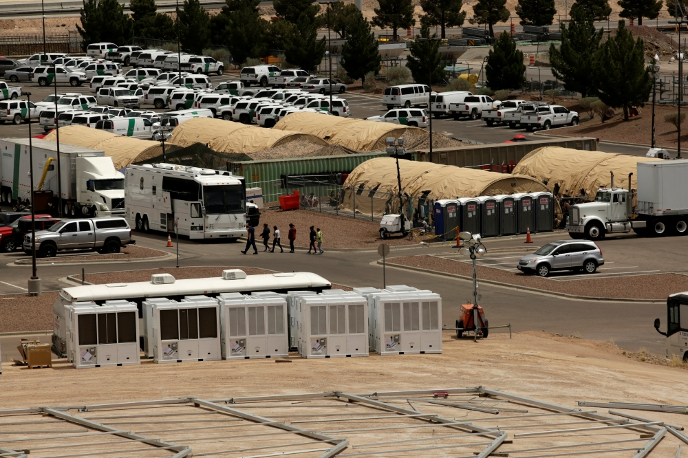 Migrant women are led by staff near an area where a temporary facility for processing migrants is being built at the US. Border Patrol headquarters in El Paso, Texas, on Monday. — Reuters