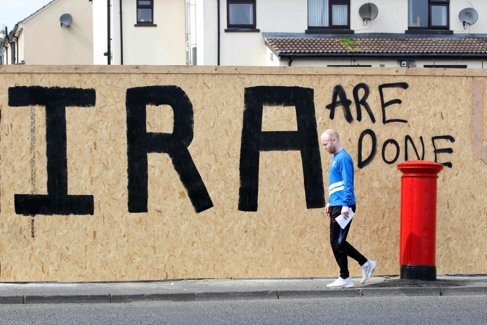 "A pedestrian walks past graffiti that has been amended to read ""IRA are done"" in the Creggan area of Derry (Londonderry) in Northern Ireland in this April 20, 2019 file photo. — AFP"