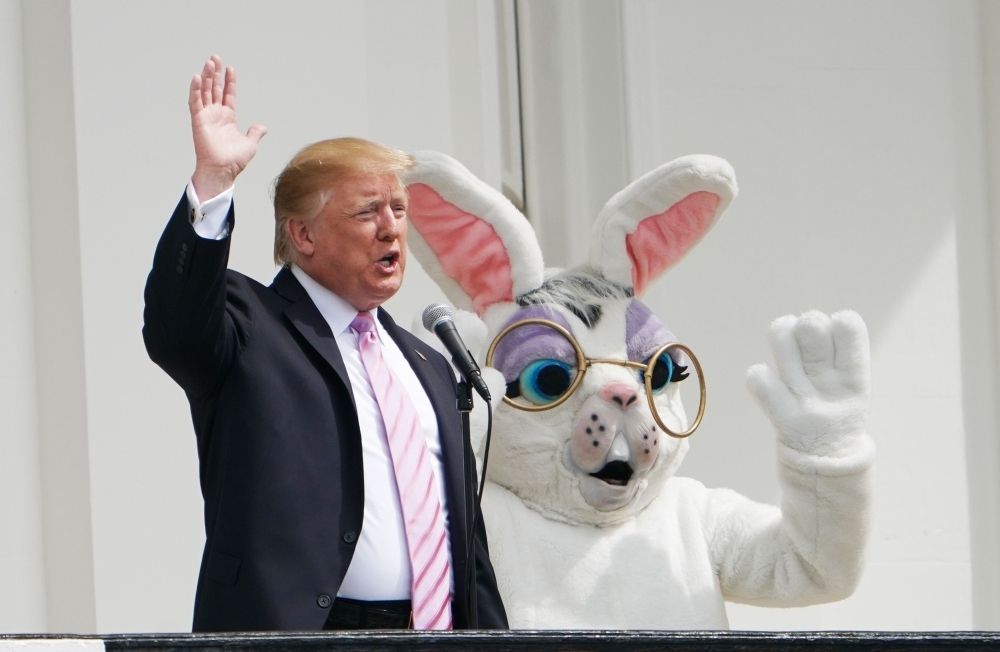 US President Donald Trump and the Easter Bunny wave during the annual White House Easter Egg Roll on the South Lawn of the White House in Washington on Monday. — AFP