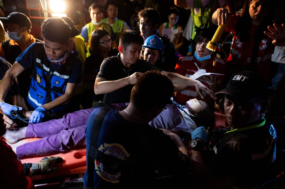 Rescue workers tend to a victim in Porac, Pampanga, after a powerful earthquake hit northern Philippines on Monday. — AFP
