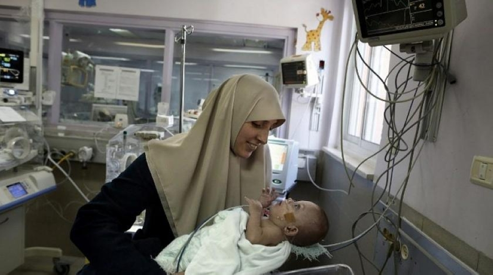 A woman carries her seven-month-old daughter at Makassed Hospital in East Jerusalem. — AFP