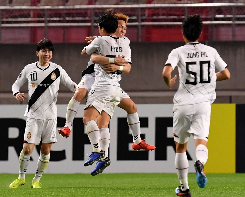 Gyeongnam's forward Takahiro Kunimoto (C, facing camera) celebrates his goal with teammates during the AFC Champions League Group E football match against Kashima Antlers at the Kashima Stadium in Kashima Wednesday. — AFP