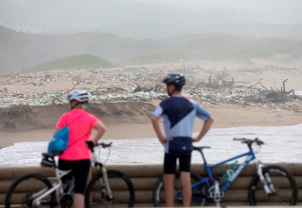 Cyclists look at debris on the beach after massive flooding in Durban, South Africa, on Wednesday. — Reuters