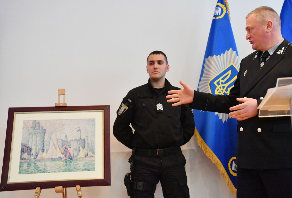 Head of the Ukrainian National Police Sergey Knyazev (R) gestures as he speaks during the presentation of the painting 'Port de la Rochelle' (1915) by French artist Paul Signac (1863-1935) at the ministry of Internal Affairs of Ukraine in Kiev. — AFP