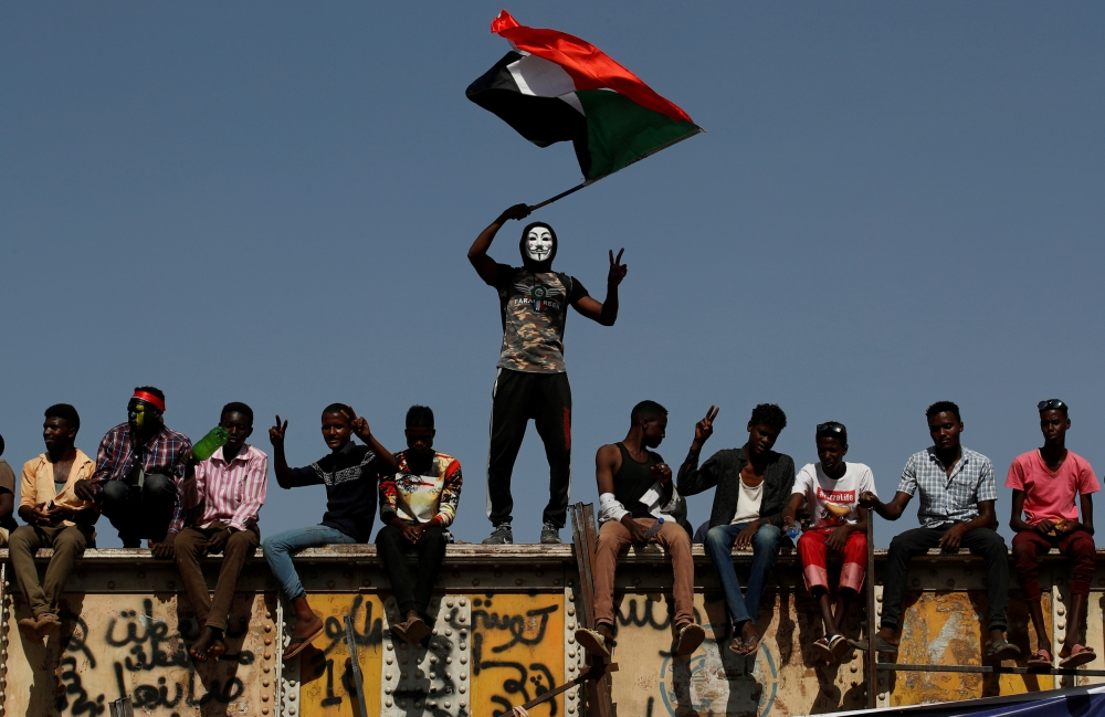 A Sudanese protester wearing a Guy Fawkes mask waves a national flag outside the defense ministry compound in Khartoum, Sudan, on Wednesday. — Reuters