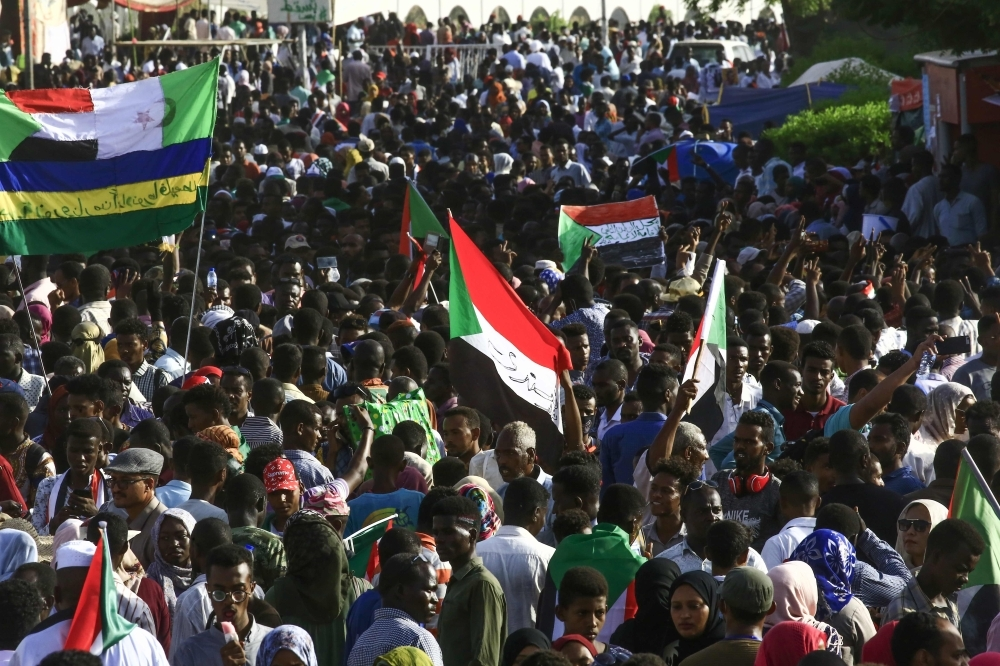 "Sudanese protesters wave the national flag during a ""million-strong"" march outside the army headquarters in the capital Khartoum on Thursday. — AFP"