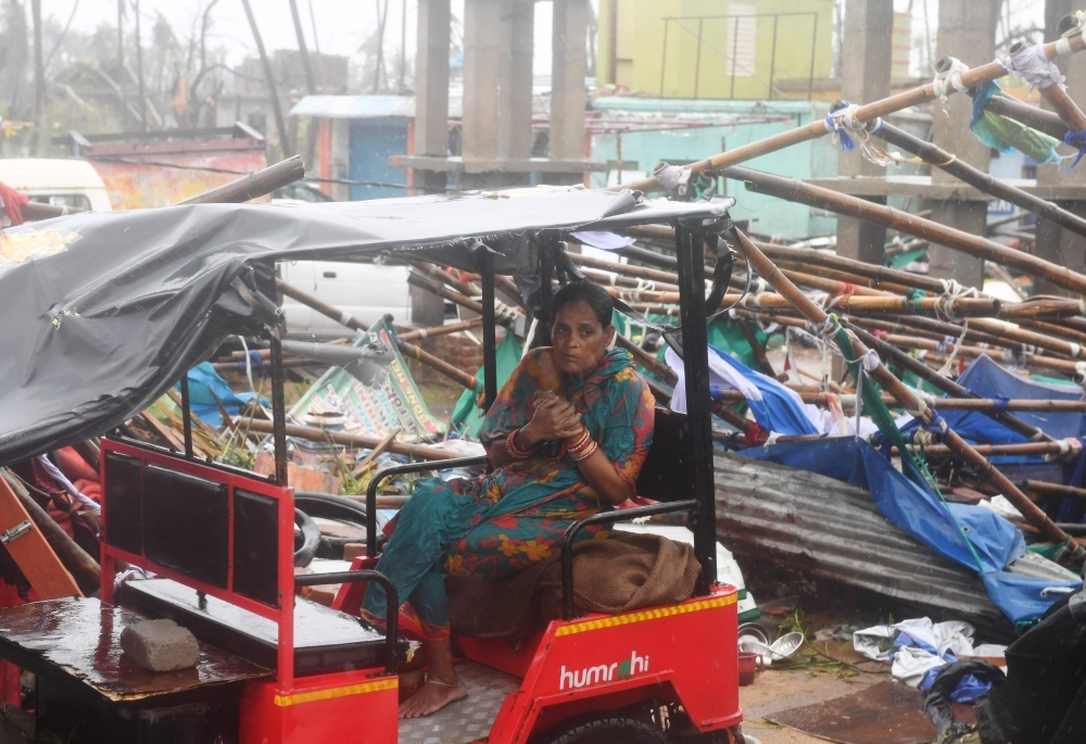 An Indian resident sits on an electric rickshaw next to a damaged structure after Cyclone Fani landfall in Puri in the eastern Indian state of Odisha on Friday. — AFP