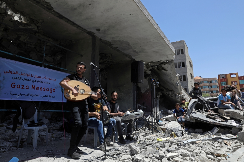 A Palestinian singer performs on Tuesday on the rubble of a building that was recently destroyed by Israeli air strikes in Gaza City during a musical event calling to boycott the Eurovision Song Contest hosted by Israel. — Reuters