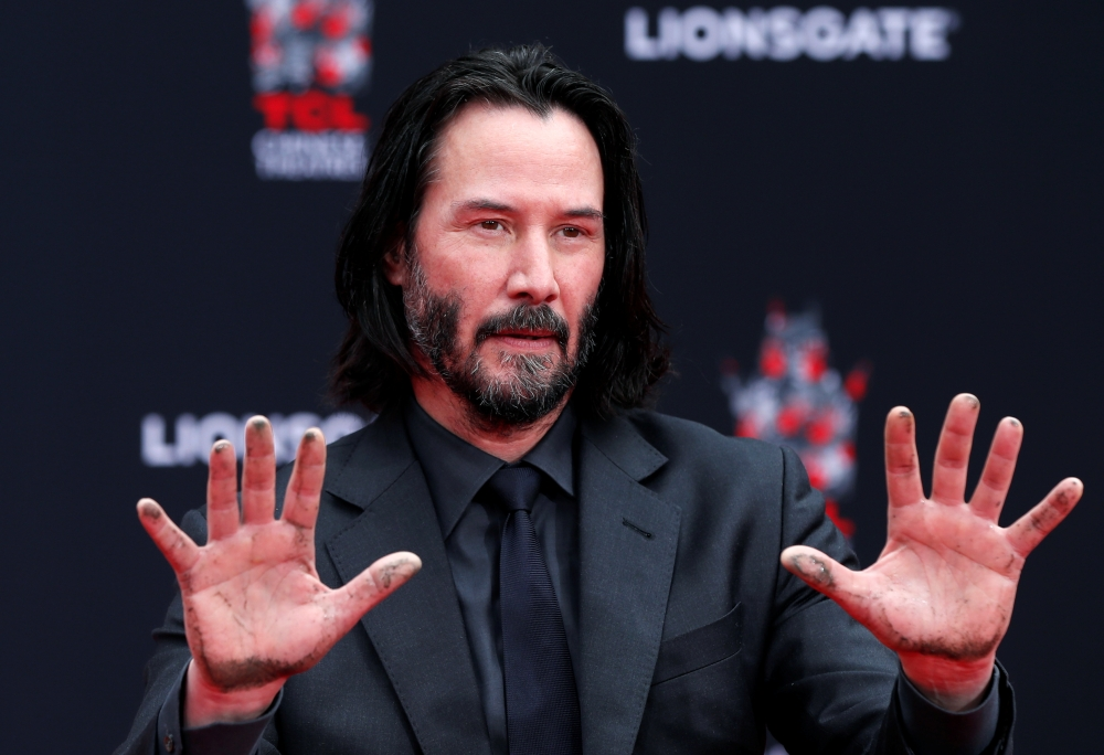 Actor Keanu Reeves gestures after putting his handprints in cement, in the forecourt of TCL Chinese theater in Los Angeles. — Reuters
