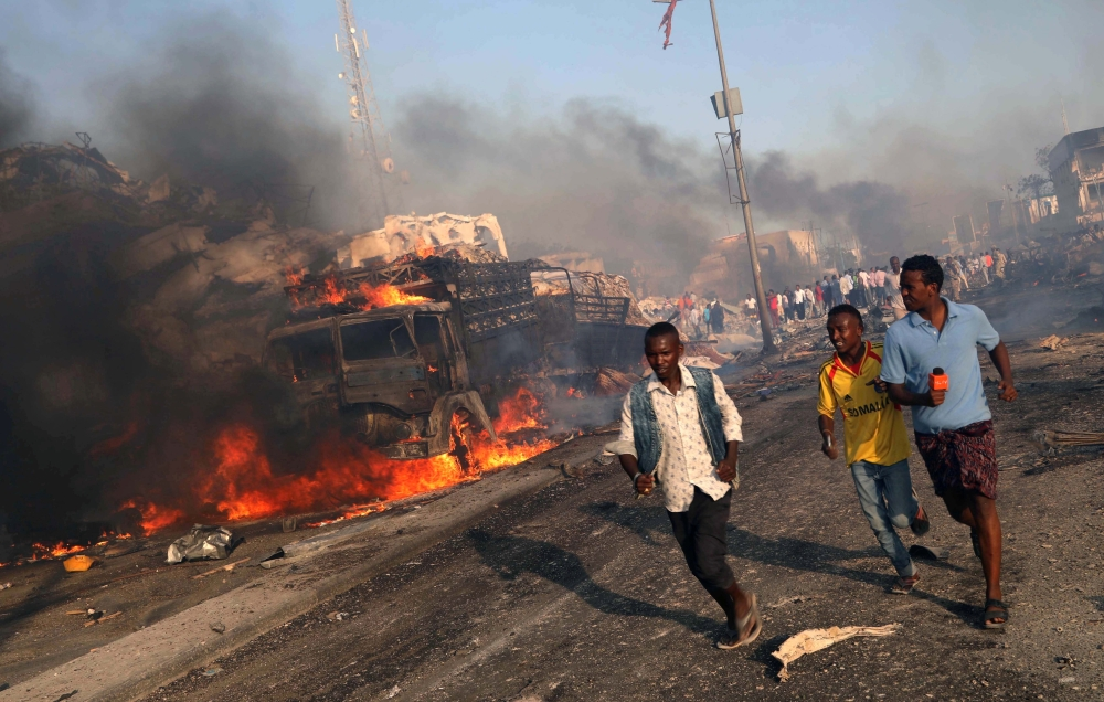 Civilians leave the scene of an explosion in KM4 street in the Hodan district of Mogadishu on October 14, 2017. — Reuters file photo