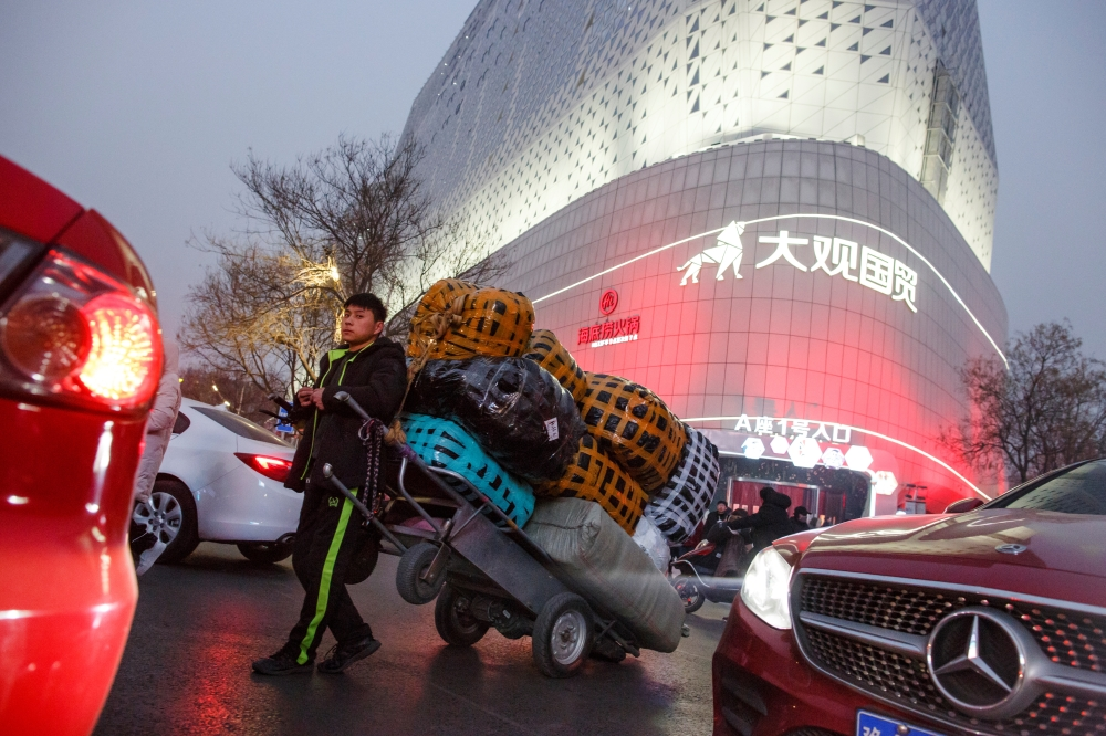 A deliveryman leans against a cart outside a wholesale market in central Zhengzhou, Henan province, China, in this file photo. — Reuters