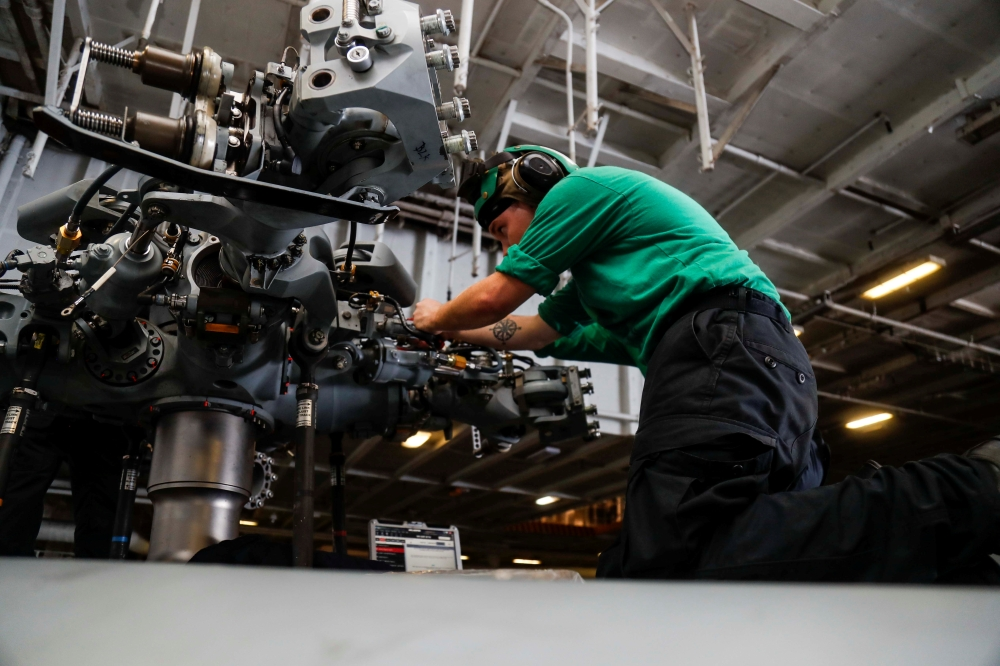 Aviation mechanic installs dampers on the main rotor head of an MH-60R Sea Hawk helicopter in the hangar bay of aircraft carrier USS Abraham Lincoln (CVN 72), in Arabian Sea, in this May 15, 2019 file photo. — Reuters