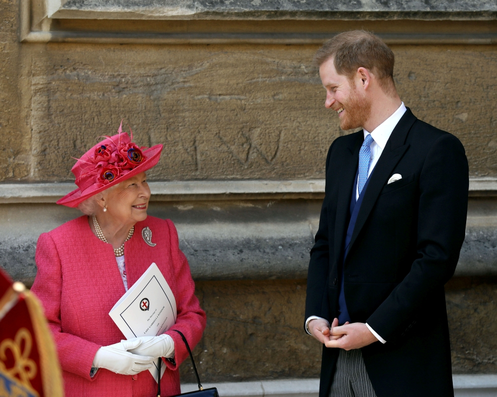 Queen Elizabeth II talks to Prince Harry as they leave after the wedding of Lady Gabriella Windsor and Thomas Kingston at St George's Chapel in Windsor Castle, near London, on Saturday. — Reuters