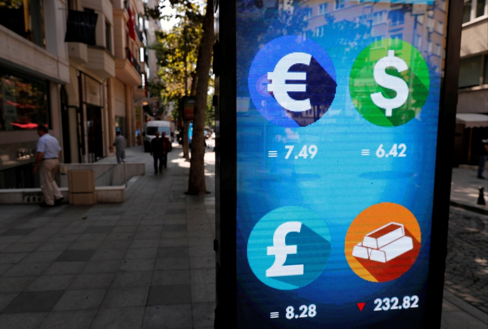 Pedestrians walk past an electronic board showing the currency exchange rates in Istanbul in this Aug. 31, 2018, file photo. — Reuters