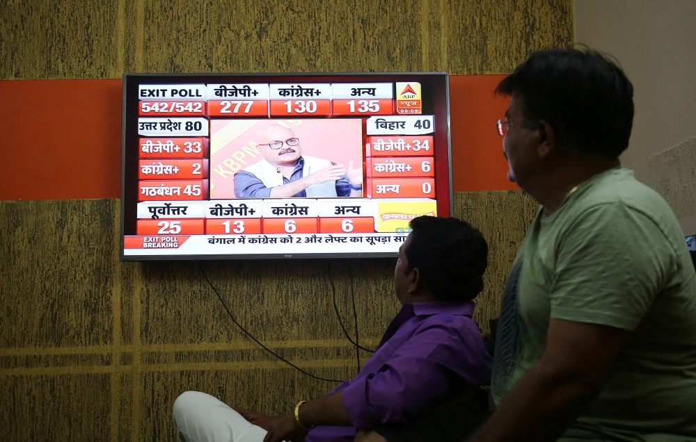 Men look at a television screen showing exit poll results after the last phase of the general election in Ahmedabad, India, May 19. - Reuters