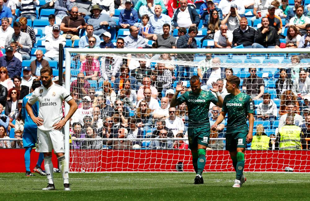 Real Betis' Jese celebrates scoring their second goal with Loren Moron as Real Madrid's Nacho looks dejected during the La Liga tie at the Santiago Bernabeu, Madrid, Spain, on Sunday. — Reuters
