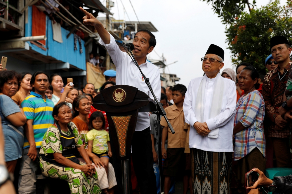 Indonesia's Incumbent President Joko Widodo gestures next to his running mate Ma'ruf Amin as they make a public address following the announcement of the last month's presidential election results at a rural area of Jakarta, May 21. - Reuters