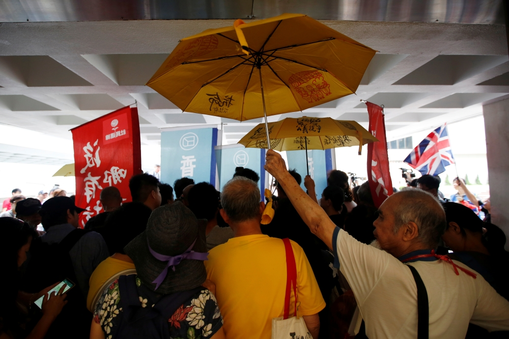 Activists hold umbrellas as Hong Kong's pro-democracy activist Joshua Wong speaks to members of the media at the High Court in Hong Kong, May 16. - Reuters