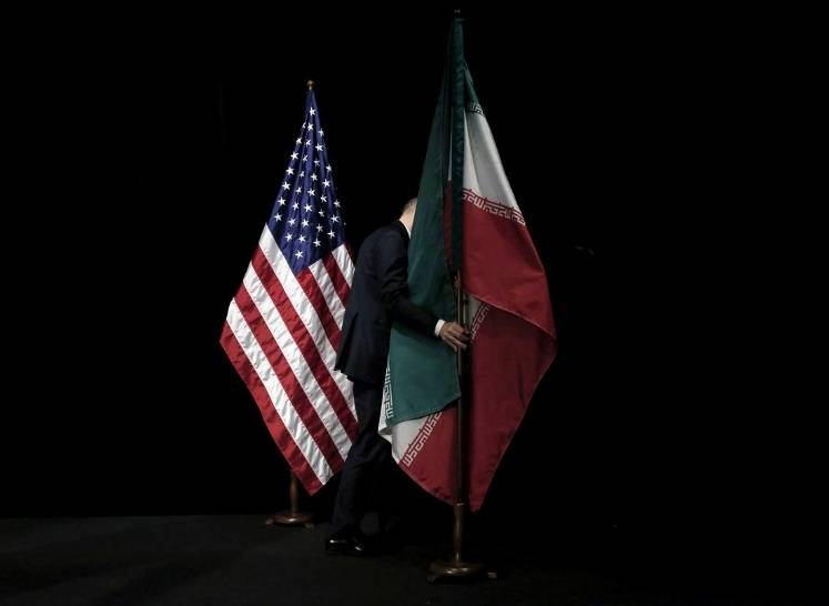 A staff member removes the Iranian flag from the stage after a group picture with foreign ministers and representatives of the US, Iran, China, Russia, Britain, Germany, France and the European Union during Iran nuclear talks at the Vienna International Center in Vienna, Austria, in this file photo. — Reuters