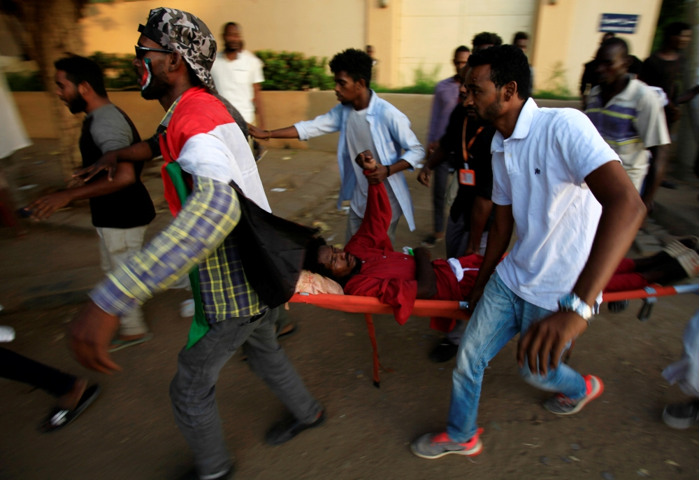 Civilians evacuate a Sudanese protester injured during demonstrations along a street in central Khartoum in this May 15 file photo. — Reuters