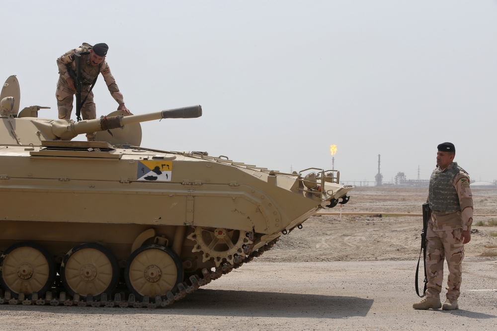 Iraqi soldiers keep guard at the entrance of the West Qurna-1 oilfield operated by Exxon Mobil near Basra, Iraq. — Reuters