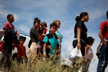 Central American migrants stand in line before entering a temporary shelter, after illegally crossing the border between Mexico and the US, in Deming, New Mexico, May 16. - Reuters