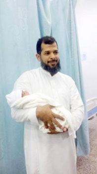 Hussain Ahmed Farie holds his baby girl after her return. — Okaz photo