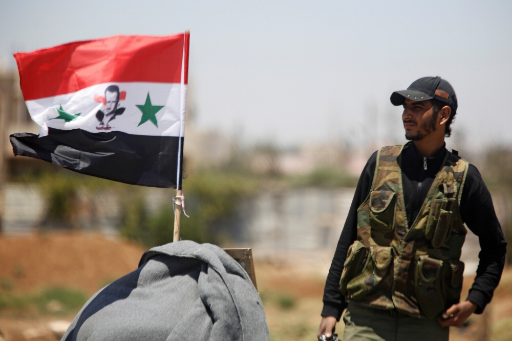 Fiel photo shows a Syrian army soldier stands next to a Syrian flag in Umm al-Mayazen, in the countryside of Deraa, Syria, — Reuters
