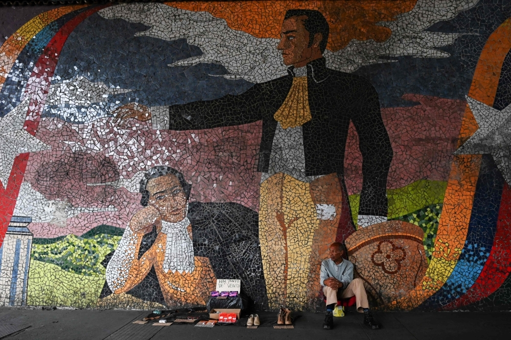 A street vendor sits in front of a mural depicting Venezuelan national hero Simon Bolivar, in Caracas on May 21. - AFP