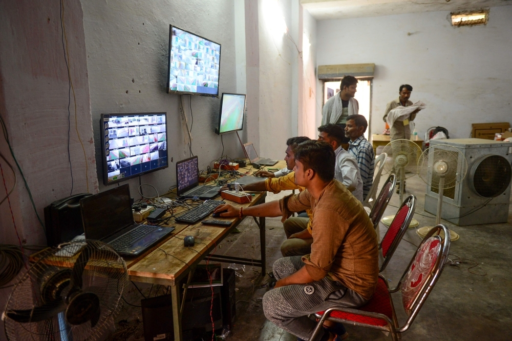 Counting agents of different political parties observe CCTV footage inside a vote counting center at Mundera Mandi where Electronic Voting Machines (EVM) are being kept on the eve of the counting day in India's general election in Allahabad, Wednesday. — AFP