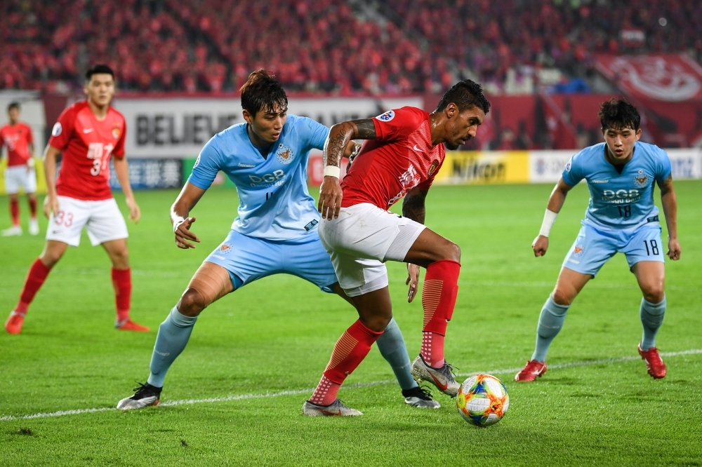 Paulinho of Guangzhou Evergrande (C) controls the ball as he is challenged by Jeong Tae-wook of Daegu FC (front L) during their AFC Champions League group stage football match in Guangzhou in China's southern Guangdong province on Wednesday. — AFP